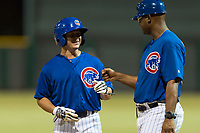 AZL Cubs 1 shortstop Clayton Daniel (25) is congratulated by first base coach Leonel Perez (66) after getting a hit during an Arizona League game against the AZL Padres 1 at Sloan Park on July 5, 2018 in Mesa, Arizona. The AZL Cubs 1 defeated the AZL Padres 1 3-1. (Zachary Lucy/Four Seam Images)