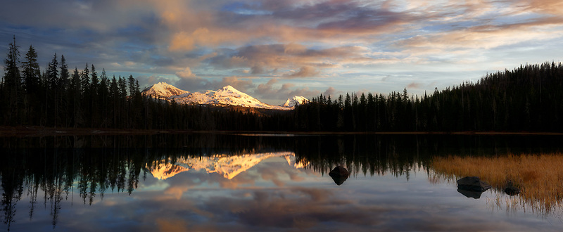Panoramic of Three Sisters Mountains  at sunset reflected in Scott Lake in Willamette National Forest.  Three Sisters Wilderness , Oregon.