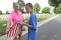 Jannie Layne, president of Bo's Blessings, and Max Williams, youth ambassador, roll a flag Friday, June 4, 2021, during the collection of flags at the National Cemetery in Fayetteville. More than 8,000 flags, provided by the National Cemetery Organization, were posted on the grave sites in recognition of Memorial Day. The flags are dried, rolled up and then stored for future use. Check out nwaonline.com/210605Daily/ and nwadg.com/photos for a photo gallery.<br /> (NWA Democrat-Gazette/David Gottschalk)
