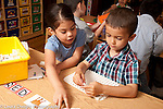 Education Preschool 4 year olds boy and girl doing activity that iinvolves cards and letters