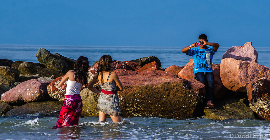 Urban Street photograph of a iPhone photographer taking ocean photographs of a girl in Puerto Vallarta Mexico.