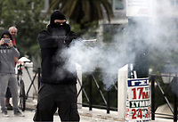 Pictured: A protester fires off a flare against police Wednesday 17 May 2017<br /> Re: Clashes between anti fourth memorandum protesters and riot police during 24 hour strike in Athens, Greece