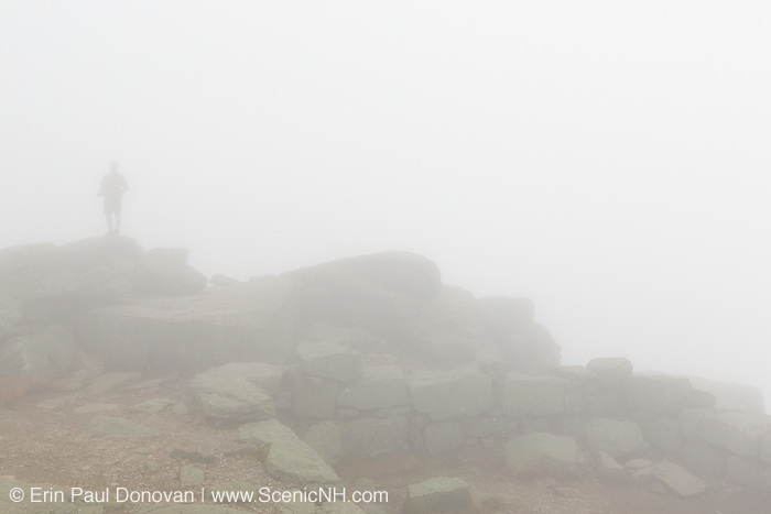 A hiker on the Appalachian Trail (Franconia Ridge Trail) on the summit of Mount Lafayette in the White Mountains, New Hampshire USA in foggy conditions during the autumn months
