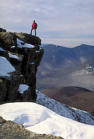 Winter mountain climber atop the summit of Mt Bondcliff in the Pemigwasset wilderness of the White Mountains of NH. This location is a long hike in Winter from the road and at the edge of a 1,000 foot drop to the valley below. Mt Bondcliff NH USA White Mo