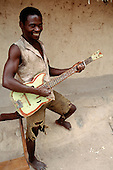 Kipili, Tanzania. Young man playing on a home-made wooden guitar.