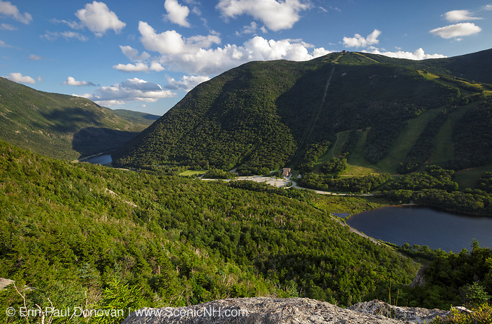Franconia Notch State Park from Eagle Cliff in the White Mountains, New Hampshire during the summer months. The parking lot for the Cannon Mountain Ski Area and Tramway occupies the site of the old Profile House, a Grand Resort (1853-1993) that burned down in 1923.