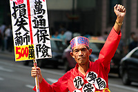 Chinese man protesting with his fist raised in the air, carrying a protest sign in the streets of Macao China