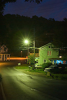 Houses along side of road at night<br />