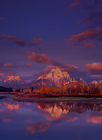 749450002v dawn light casts alpenglow on the teton range reflected in the snake river at the oxbow bend of the snake river on an autumn morning with fall colored aspens in grand tetons national park wyoming