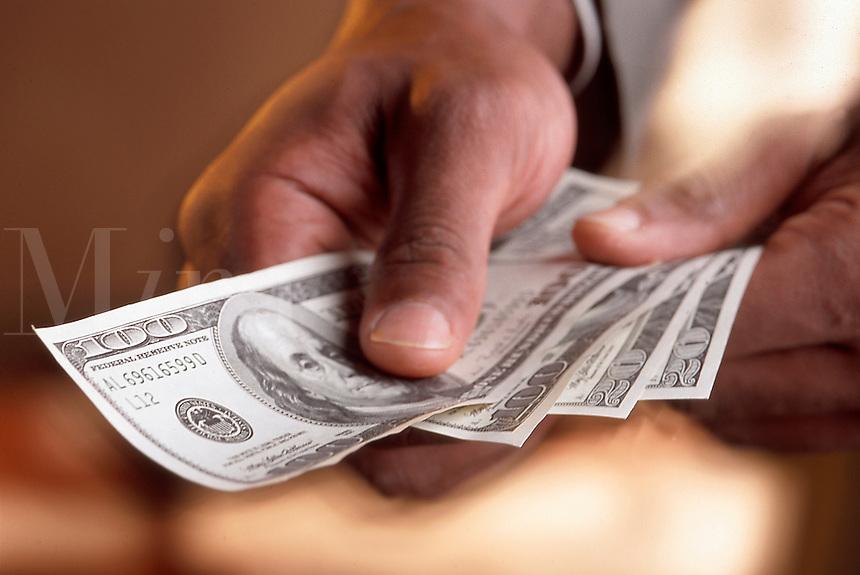 A hand holding a $100 dollar bills.