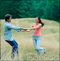 Couple, holding hands, playing in a field<br />