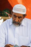 Oman, Buraimi, Arab man, seated, with traditional kummah cap