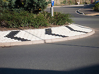 Bricks used to show direction of traffic at a roundabout.  Ashford, Kent.
