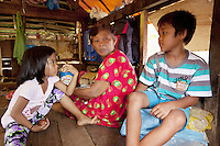 Philippines. Province Eastern Samar. Hernani. Barangay (neighbourhood) Carmel. Traditional hut. A grandmother and her granchildren, a boy and a girl, are seated on the floor of their one room house. The roof and the walls of their house were damaged by typhoon Haiyan's winds. Typhoon Haiyan, known as Typhoon Yolanda in the Philippines, was an exceptionally powerful tropical cyclone that devastated the Philippines. Haiyan is also the strongest storm recorded at landfall in terms of wind speed. Typhoon Haiyan's casualties and destructions occured during a powerful storm surge, an offshore rise of water associated with a low pressure weather system. Storm surges are caused primarily by high winds pushing on the ocean's surface. The wind causes the water to pile up higher than the ordinary sea level. 25.11.13 © 2013 Didier Ruef