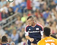 New England Revolution forward Chad Barrett (9) heads the ball.  In a Major League Soccer (MLS) match, Houston Dynamo (orange) defeated the New England Revolution (blue), 2-1, at Gillette Stadium on July 13, 2013.