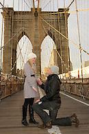 Guy on his knees proposing to girlfriend on the pedestrian walkway of the Brooklyn Bridge.