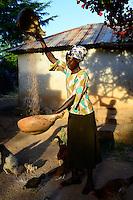 KENIA, ADS Anglican Development Services of Mount Kenya East, Stadt Embu, Dorf Gichunguri, Projekt Regenwasserauffang an einem Felsen und Speicherung in Tanks zur Nutzung in Duerreperioden, Agnes Irima, 44 Jahre, auf ihrem Hof, trennt die Spreu vom Sorghum Korn