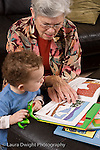 2 year old toddler boy at home with grandmother interaction read to from picture book vertical she takes care of him when parents work