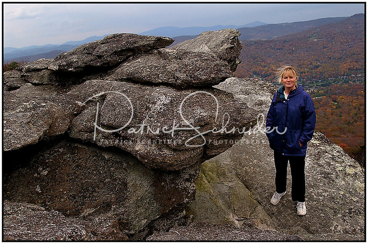 A woman stands near the highest point on Grandfather Mountain, in Avery County, NC. Grandfather Mountain is a popular mountain and state park located near Linville, North Carolina. It is the highest peak in the eastern escarpment of the Blue Ridge Mountains. Model released
