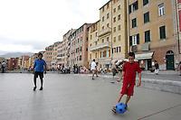 Bambini giocano a pallone sul lungomare di Camogli. Sullo sfondo i caratteristici alti palazzi.<br /> Children play football in Camogli. In background, typical tall houses.<br /> UPDATE IMAGES PRESS/Riccardo De Luca