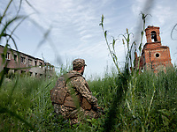 Sergeant Kyryl (45) keeps a watch towards the horizon, looking out for any enemy activities in the frontline city of Pisky, located in the outskirts of Donetsk, the stronghold of the Russian-backed separatista. Not a single house in the town stands untouched by the war. According to the Ukranian govenment soldiers based here, not a day goes by without attacks from the separatist forces, either from snipers or shelling.
