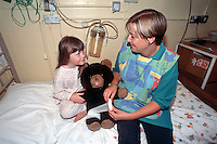 Child confined to bed in hospital being shown by a nurse how the bandage will be applied to her leg after her operation by showing children how procedures are done on a teddy bear or a doll helps them understand and relax. This image may only be used to portray the subject in a positive manner..©shoutpictures.com..john@shoutpictures.com