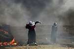 Palestinian women hurl stones towards Israeli security forces during clashes at tents protest where Palestinians demand the right to return to their homeland, in east of Gaza city on April 20, 2018. Photo by Atia Darwish