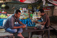Bali, Indonesia.  Two Men Having Breakfast at a Roadside Refreshment Stand, Early Morning.