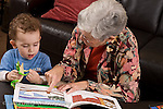 2 year old toddler boy at home with grandmother interaction read to from picture book language development grandmother talking and pointing to picture horizontal