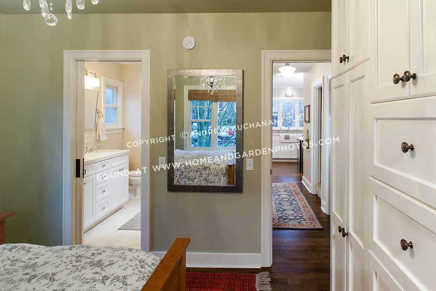 Newly remodeled home with a wall of built-ins in the master bedroom and dark wood floors tying the rooms together