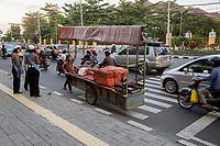 Yogyakarta, Java, Indonesia.  Vendor Pushing Cart against Evening Traffic,  Jl. Laksda Adisucipto Street.