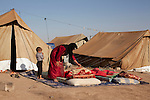 DOMIZ, IRAQ: A mother wakes her children who were sleeping outside in the Domiz refugee camp...Over 7,000 Syrian Kurds have fled the violence in Syria and are living in the Domiz refugee camp in the semi-autonomous region of Iraqi Kurdistan...Photo by Ali Arkady/Metrography