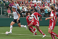 USWNT'S Abby Wambach (20) dribbles the ball downfield as Canada's Jodi-Ann Robinson (10)     and Candace Chapman (9) give chase. The U.S. Women's National Team defeated Canada 1-0 in a friendly match at Marina Auto Stadium in Rochester, NY on July 19, 2009. Abby Wambach of the USWNT scored her 100th career goal in the second half..