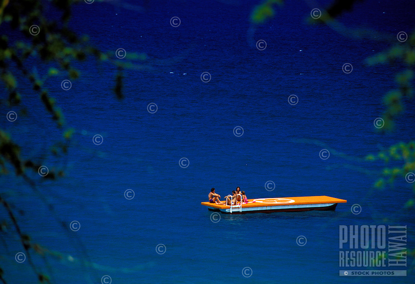 Three adults and a child on a floating swim deck at Mauna Kea Beach on the Big Island