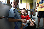 A nurse holds a young disabled child in the Agent Orange children's ward of Tu Du Hospital in Ho Chi Minh City, Vietnam.  About 500 of the 60,000 children delivered each year at the maternity hospital, Vietnam's largest, are born with deformities. some because of Agent Orange, according to doctors. About 60 of them currently live on the ward, ranging in age from newborns to young people in their 30s. May 1, 2013.