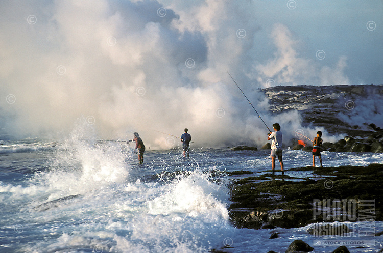 EDITORIAL ONLY. Catching fish from the rocks as lava approaces the sea in Kalapana