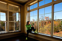 A woman holding a coffee cup looks out through a bank of windows into the autumn mountainside. Photo taken in Asheville NC's Biltmore Park Town Square, a planned community of residential living, office spaces and shopping.