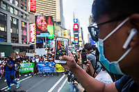 """NEW YORK, NY - JULY 26: A young man takes a photo with his cell phone of the huge crowd of protesters marching in Times Square in New York, NY on July 26, 2020. Hundreds of New York activists participated in a march. to condemn what they see as excessive focus by federal authorities in Portland, Oregon and continue to support the different movements of """"Black Lives Matter"""" (Photo by Pablo Monsalve / VIEWpress via Getty Images)"""