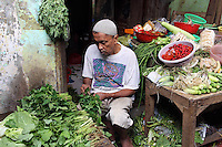 A vegetable seller sits outside his shop in central Jakarta.<br /> <br /> To license this image, please contact the National Geographic Creative Collection:<br /> <br /> Image ID:  1588052<br />  <br /> Email: natgeocreative@ngs.org<br /> <br /> Telephone: 202 857 7537 / Toll Free 800 434 2244<br /> <br /> National Geographic Creative<br /> 1145 17th St NW, Washington DC 20036