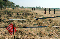"""Angola. Cuando Cubango. Mavinga. The death's-head sign says """"Watch for mines, Danger"""".  Mines (personal, anti tanks,..) are laid in the field. Soldiers walk on the sandy roadtrack. © 2002 Didier Ruef"""