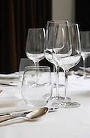 Wine and water glasses and cutlery on white linen table cloth at the restaurant xxxx Paris, France.