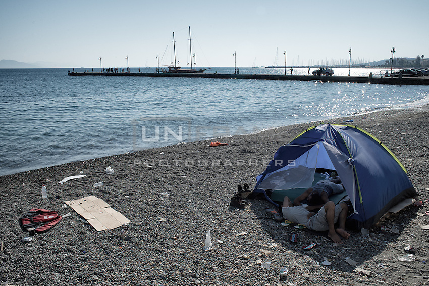 Small tent on a littered, gravel beach where two Syrians try to sleep. Every day they go to the police station in hope of receiving their permit to go to Athens.  Kos, Greece. Sept. 6, 2015
