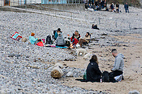 Pictured: People rest on the beach in Langland. Friday 16 April 2021<br /> Re: People enjoy an evening out after Covid-19 lockdown rules were relaxed, in Swansea Bay, Wales, UK.