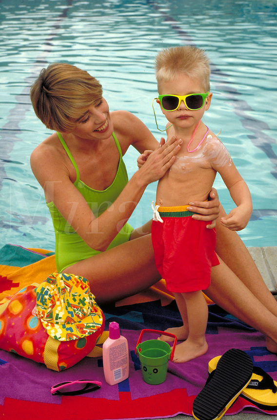CAUCASIAN MOTHER APPLYING SUNSCREEN TO HER SON(4) AT THE POOL. MOTHER AND SON (4). OAKLAND CALIFORNIA.