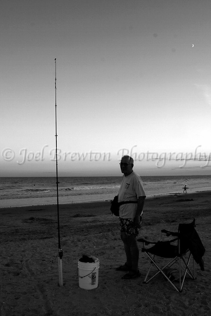 A fisherman finishes up his summer evening catch on the shores of Ocean City, NJ.