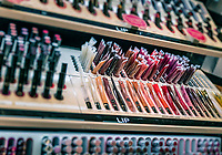 Lip gloss display in a Sephora personal care and beauty store.