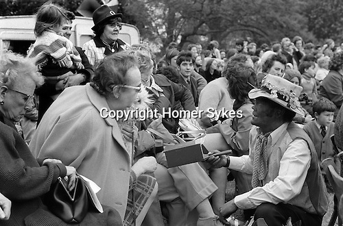 Ickwell May Day Bedfordshire 1973 UK . A Moggie also called a Mogger with 'black face', takes around a collecting box  Mr Barry Edwards is the Moggie.