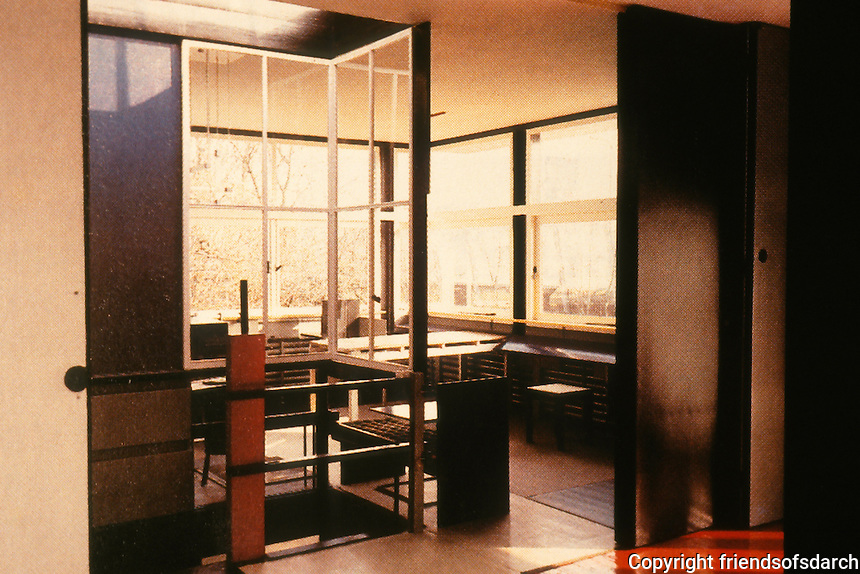 Gerrit Rietveld: Schroder House. Same view: sliding partitions partly closed and the moveable windon on staircase railings in position. To the left, closed doors of Mrs. Schroder's bedroom.