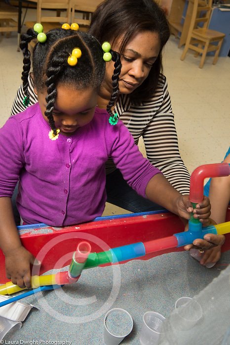Education preschool sandbox preschool girl playing facilitated by female teacher who is holding construction for her