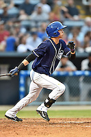 Asheville Tourists shortstop Emerson Jimenez #14 swings at a pitch during a game against the Kannapolis Intimidators at McCormick Field on June 5, 2014 in Asheville, North Carolina. The Intimidators defeated the Tourists 5-3. (Tony Farlow/Four Seam Images)